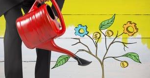 Das Halten der Gießkanne und des Zeichnens von kommerziellen Grafiken auf Anlage verzweigt sich auf Wand Stockbilder