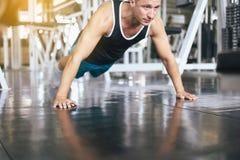 Das Handeln des starken Mannes drückt und Übungen auf Boden an der Turnhalle hoch stockbild