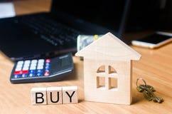 Das Haus auf dem Schreibtisch des Grundstücksmaklers Immobilien kaufen und verkaufend Erwerb des Eigentums und der Investition de stockbild