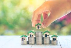 Das Haus, das auf Münzen Männer ` s Hand gesetzt wird, plant Einsparungensgeld von Münzen, um ein Hauptkonzeptkonzept für Eigentu stockfoto