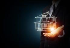 Das Haus in den menschlichen Händen Lizenzfreie Stockfotos