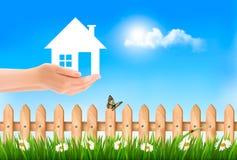 Das Haus in der Hand auf grünem natürlichem Hintergrund Stockfotografie