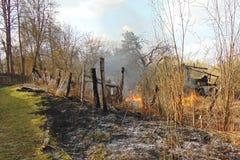 Das Haus gebrannt im Gegensatz zu dem grünen Gras Stockfoto