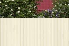 Das Haus mit einem roten Dach und einem Garten wird durch einen hohen Whit blockiert Stockfotografie
