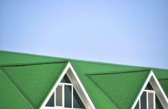 Das Haus mit Plastikfenstern und einem grünen Dach des Wellblechs Stockfotografie