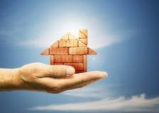 Das Haus von Ziegelsteinen in der Hand auf blauem Himmel Lizenzfreie Stockbilder