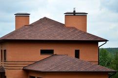 Das Haus wird mit hochwertiger Deckung von Schindelbitumenfliesen ausgerüstet Ein gutes Beispiel der perfekten Deckung Das Dach i stockfotos