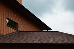 Das Haus wird mit hochwertiger Deckung von Schindelbitumenfliesen ausgerüstet Ein gutes Beispiel der perfekten Deckung Das Dach i stockfoto
