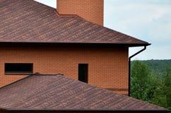 Das Haus wird mit hochwertiger Deckung von Schindelbitumenfliesen ausgerüstet Ein gutes Beispiel der perfekten Deckung Das Dach i lizenzfreies stockfoto