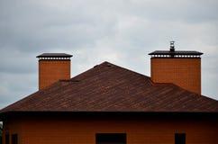 Das Haus wird mit hochwertiger Deckung von Schindelbitumenfliesen ausgerüstet Ein gutes Beispiel der perfekten Deckung Das Dach i stockbild