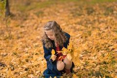 Das Herbstmädchen, das mit buntem Fall glücklich ist, lässt das Fallen stockfoto