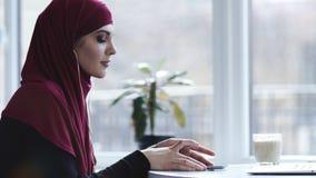 Das herrliche Arabisch, das mit hijab weiblich schaut, setzt Kopfhörer in ihre Ohren ein und fängt an, ihre Lieblingsmusik zu hör stock video