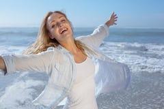 Das herrliche blonde Verbreiten bewaffnet heraus am Strand Lizenzfreies Stockfoto