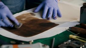 Das Herstellungsverfahren eine lederne Geldbörse handgemacht Der Meister malt ein Stück Leder im Braun handmade stock video footage