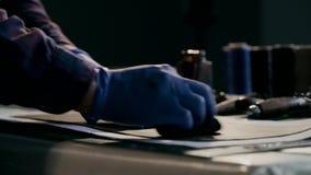 Das Herstellungsverfahren eine lederne Geldbörse handgemacht Der Meister malt ein Stück Leder im Braun handmade stock footage