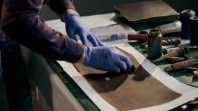 Das Herstellungsverfahren eine lederne Geldbörse handgemacht Der Meister malt ein Stück Leder im Braun handmade stock video