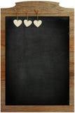 Das Herz Tafel-des weißen Liebes-Valentinsgrußes, das am Holzrahmen hängt Stockfotos