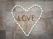 Das Herz von weißen Steinen auf der Holzoberfläche lizenzfreie stockfotografie