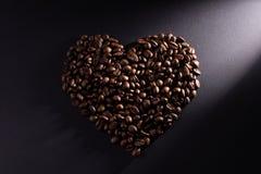 Das Herz wird vom Kaffee mit einem diagonalen Strahl gemacht, der rechts erhellt wird stockbilder