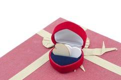 Das Herzsymbol, das vom Holz im roten Ringkasten auf roter Geschenkbox mit dem Band gemacht wird von gemacht wird, bereiten Papie Stockfoto