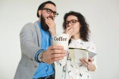 Das Hippie-Team, das gähnt, ermüdete mit der Kaffeetasse, die auf Weiß lokalisiert wurde Stockbild