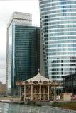 Das historische Karussell zwischen Wolkenkratzern Stockfotografie