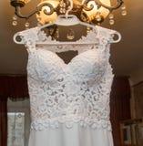 Das Hochzeitskleid, das an einem Aufhänger hängt Lizenzfreie Stockfotos