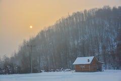 Das Holzhaus in einer Waldfläche im Winter Stockbild