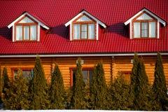 Das Holzhaus mit einem roten Dach und Fenstern Stockbilder