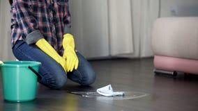 Das Hotelmädchenknienglauben ermüdet vom Waschen des schmutzigen Bodens befleckt, Desinfizierer Lizenzfreie Stockfotografie