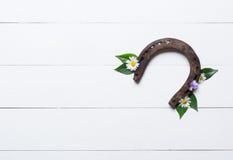 Das Hufeisen, benutzt und mit Rost, auf Weiß malte Holz, Symbol für lizenzfreie stockfotos
