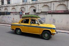 Das ikonenhafte gelbe Botschaftertaxi Kolkata mit einem Grasdach Stockfotografie