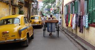 Das ikonenhafte gelbe Botschaftertaxi Kolkata und eine Hand zogen Rikscha Stockbild
