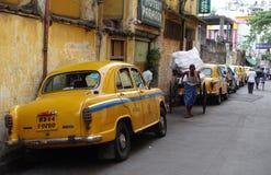 Das ikonenhafte gelbe Botschaftertaxi Kolkata und eine Hand zogen Rikscha Stockfotos