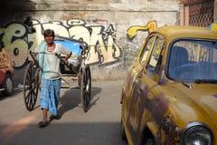 Das ikonenhafte gelbe Botschaftertaxi Kolkata und eine Hand zogen Rikscha Lizenzfreie Stockbilder