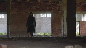 Das ist ein defektes verlassenes Gebäude des netten Rahmens Der Raum ist ein Mann in einem Regenmantel und in einem Hut stock footage