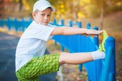 Das jugendlich Handeln des Jungen trägt Übungen auf einem Stadion zur Schau Lizenzfreie Stockfotografie