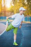 Das jugendlich Handeln des Jungen trägt Übungen auf einem Stadion zur Schau Lizenzfreies Stockbild