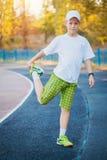 Das jugendlich Handeln des Jungen trägt Übungen auf einem Stadion zur Schau Lizenzfreie Stockfotos