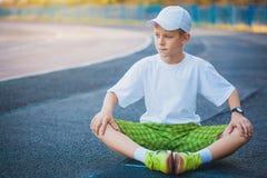 Das jugendlich Handeln des Jungen trägt Übungen auf einem Stadion zur Schau Lizenzfreie Stockbilder