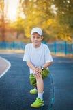 Das jugendlich Handeln des Jungen trägt Übungen auf einem Stadion zur Schau Stockfoto