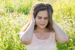 Das jugendlich Mädchen schließt seine Ohren und das Gesichtes Verziehen Gesichtes Verziehen in den Schmerz Stockfoto