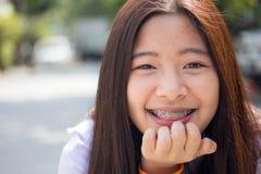 Das jugendlich schöne glückliche Mädchen des thailändischen Studenten und entspannen sich in der Schule Stockfotografie