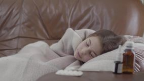Das jugendliche kranke Mädchen des Porträts, das auf dem Sofa zu Hause bedeckt wird mit einer Decke liegt, ist sie kalt Nasenspra stock video footage
