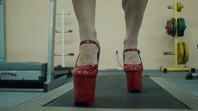 Das junge athletische Mädchen, athletisch, führt eine Übung auf einer Tretmühle durch Auf ihren Füßen trug sie Schuhe auf einem H stock footage
