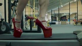 Das junge athletische Mädchen, athletisch, führt eine Übung auf einer Tretmühle durch Auf ihren Füßen trug sie Schuhe auf einem H stock video