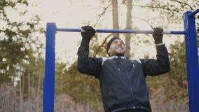 Das junge athletische Mannhandeln zieht Übung im Winterpark draußen hoch stock video footage