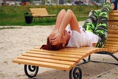 Das junge attraktive Mädchen liegt auf einem Wagenaufenthaltsraum auf dem Stadtstrand und dem reizenden Lächeln Stockbild