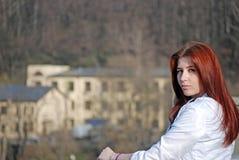 Das junge attraktive Mädchen mit dem roten Haar in einer Weißjacke kostet auf der Brücke vor dem hintergrund des alten Hauses im  Stockfotografie