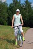 Das junge attraktive Mädchen reitet ein Fahrrad im Sommer Trägt Lebensart zur Schau Lizenzfreie Stockfotos